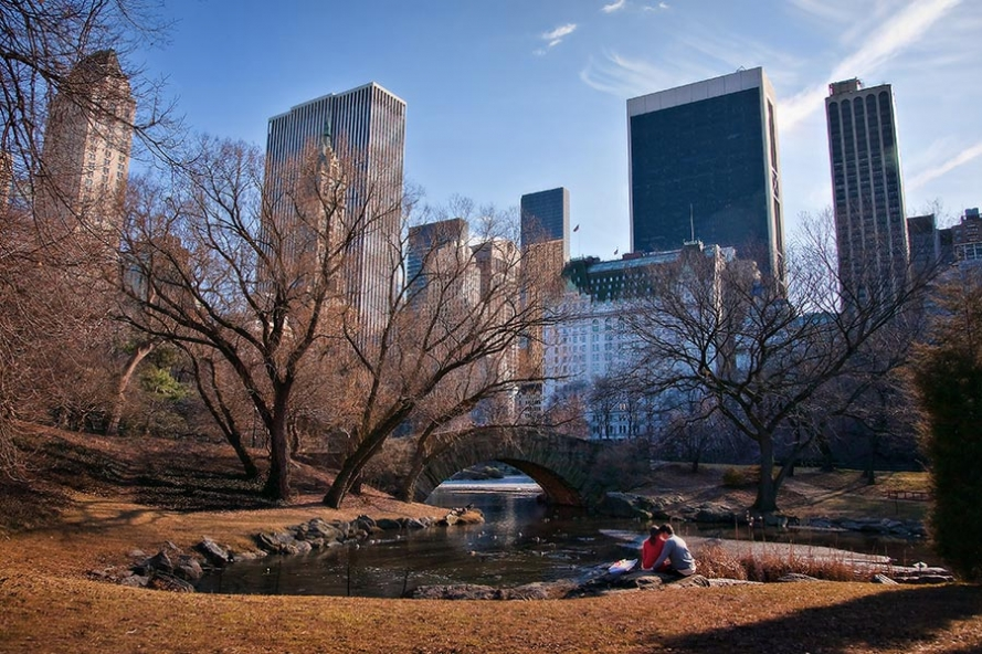 young couple sit by a lake in Central Park Manhattan New York