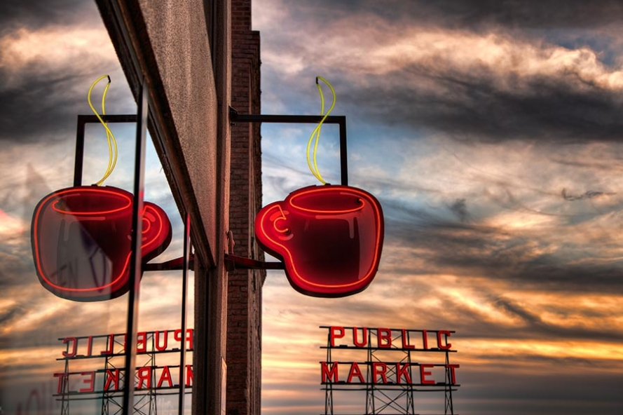 neon coffee cup sign in Seattle with sunset sky behind