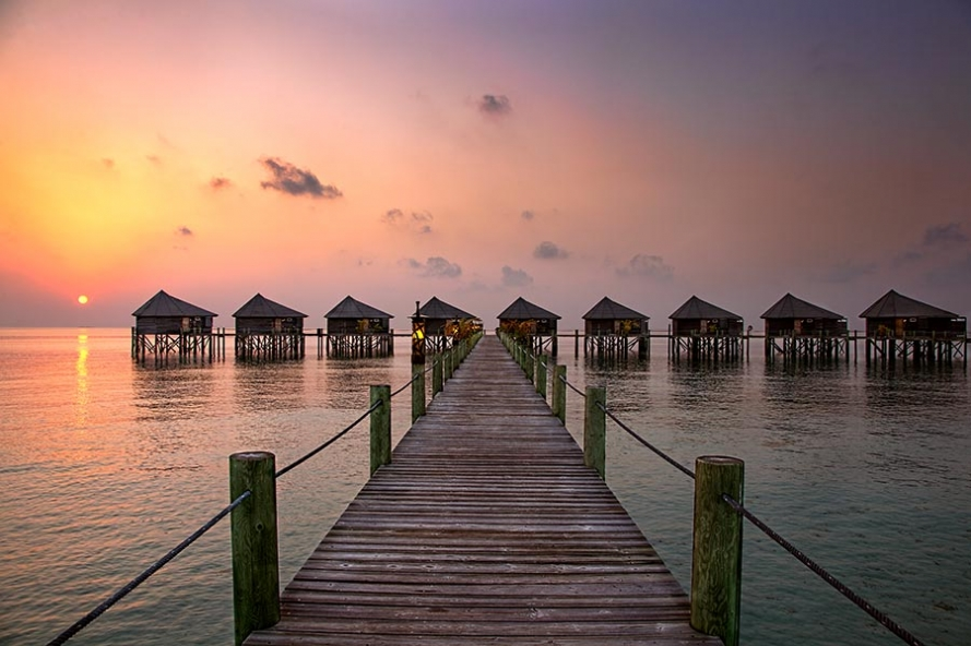sunrise over water villas on the island of komandoo in the maldives