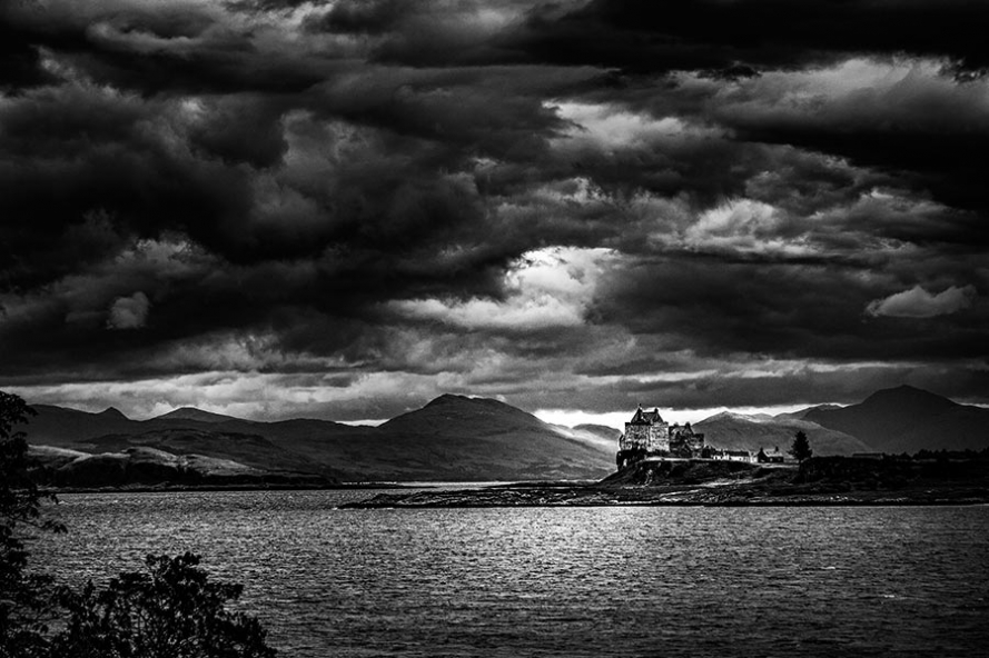 moody black and white photograph of dark skies over duart castle on the isle of mull in scotland