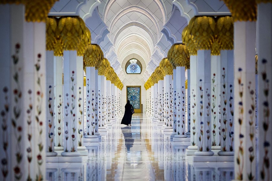 woman walking at sheikh zayed grand mosque in aub dhabi